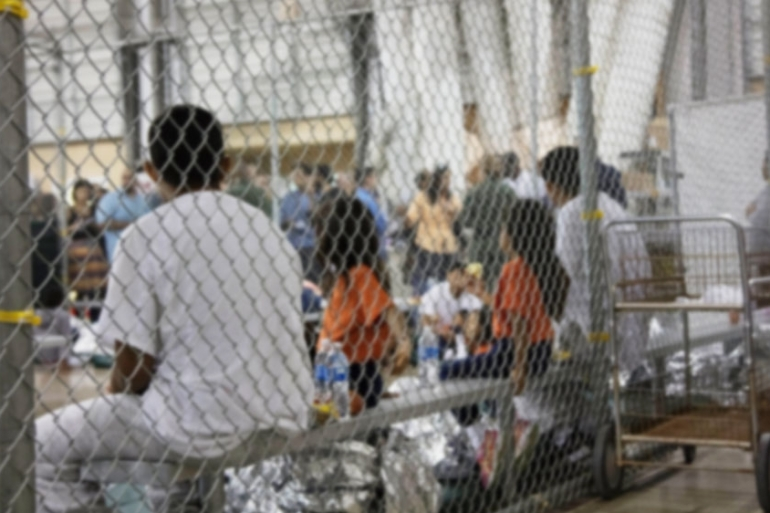 In this June 17, 2018 file photo provided by US Customs and Border Protection, people who've been taken into custody related to cases of irregular entry into the US, sit in one of the cages at a facility in McAllen, Texas [File: Handout/US Customs and Border Protection''s Rio Vally Sector/AP Photo]