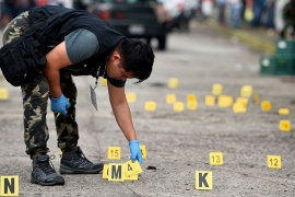 A forensic technician looks for bullet casings on the ground at a crime scene after a shooting in the municipality Tuzamapan, in the Mexican state of Veracruz [File: Yahir Ceballos/Reuters]