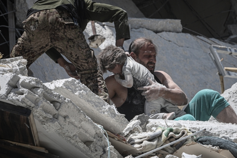 A Syrian man saves a baby under the debris following air raids in Arihah district of Idlib, northwest Syria [Muhammed Said/Anadolu Agency]