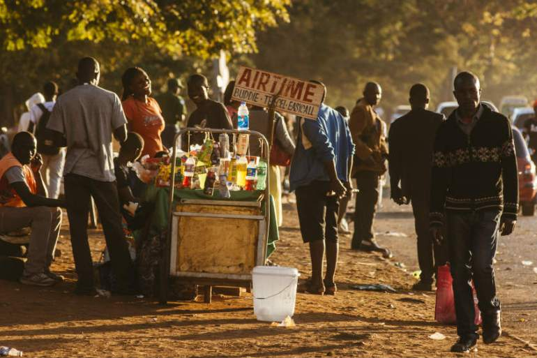 A street vendor sells food and mobile phone vouchers on a roadside in Harare [Waldo Swiegers/Bloomberg]