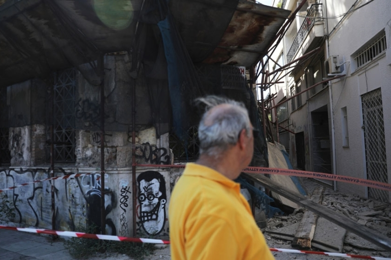 A man walks past damaged buildings in downtown Athens following the earthquake [Alkis Konstantinidis/Reuters]