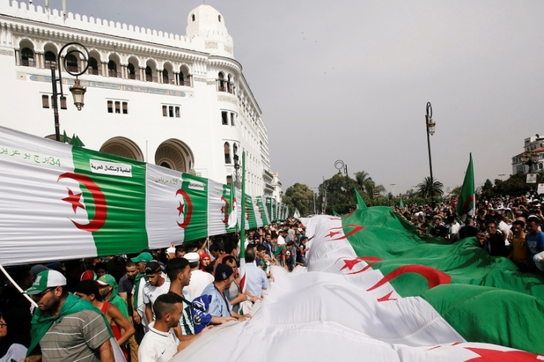 Crowds wearing Algerian flags on their shoulders, heads and waists poured onto the streets of the capital Algiers on Friday [Ramzi Boudina/Reuters]