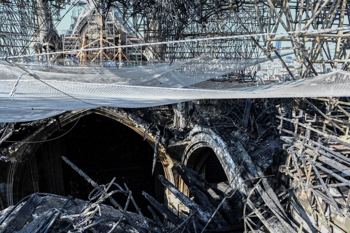 Parts of a destroyed ribbed vault and scaffolding are seen in the Notre Dame de Paris Cathedral. [Stephane De Sakutin/Pool/AFP]