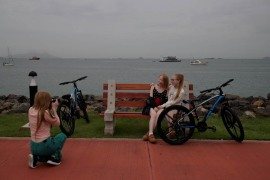 Aydili Gonzalez, left, 23, takes pictures of her sisters Ceily, centre, 18, and Yaili, right, 23, at the Causeway Islands, in Panama City, Panama. [Bienvenido Velasco/EPA]