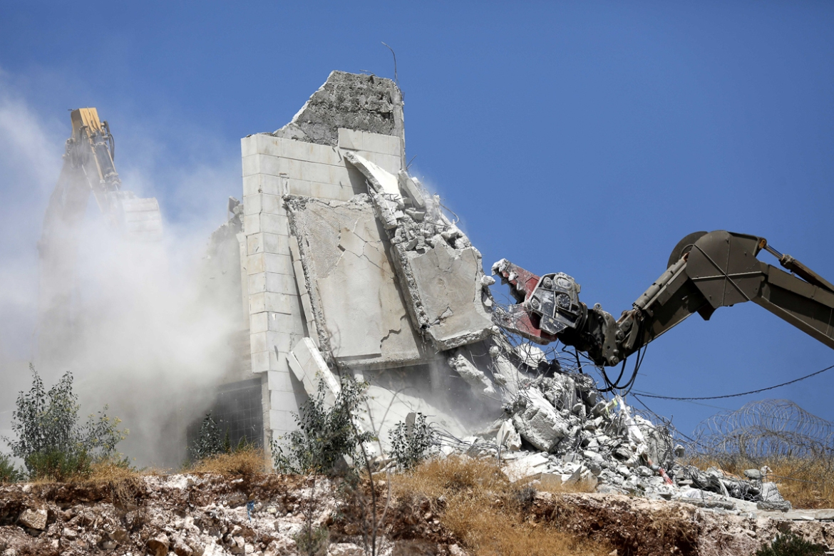 An Israeli army excavator demolishes a building in the village of Sur Baher. The sprawling village straddles the line between occupied East Jerusalem and the occupied West Bank. [Abed al-Hashlamoup/EPA]
