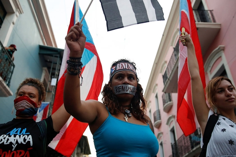 Women wave Puerto Rican flags during a protest calling for the resignation of Governor Rossello in San Juan [Marco Bello/Reuters]