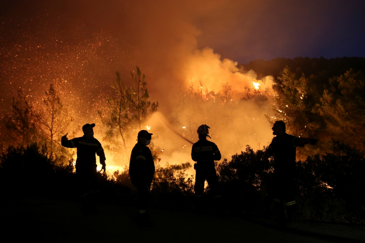 Firefighters try to extinguish a wildfire burning near the village of Makrimalli. [Costas Baltas/Reuters]