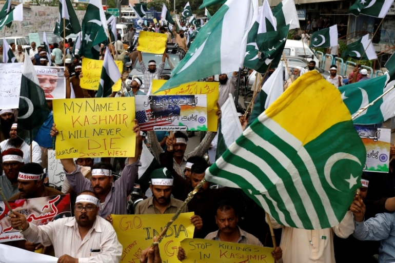 People hold flags and signs in solidarity with the people of Kashmir during a rally in Karachi on Monday [Akhtar Soomro/Reuters]