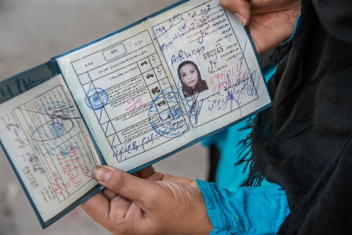 A woman who attended a driving course provided by Nove Onlus shows her license. [Alessio Mamo/Al Jazeera]