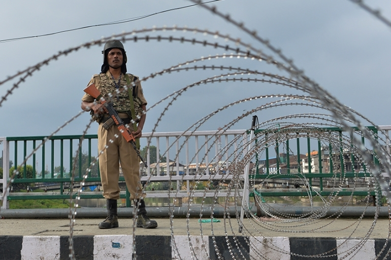 A security personnel stands guard on a street during a lock down in Srinagar [Sajjad Hussain/AFP]