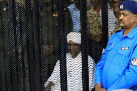Sudan's former president Omar al-Bashir sits guarded inside a cage at the court where he is facing corruption charges in Khartoum [File: Mohamed Nureldin Abdallah/Reuters]