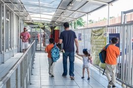 A father and his children walk back to Mexico after school lets out [Eline van Nes/Al Jazeera]