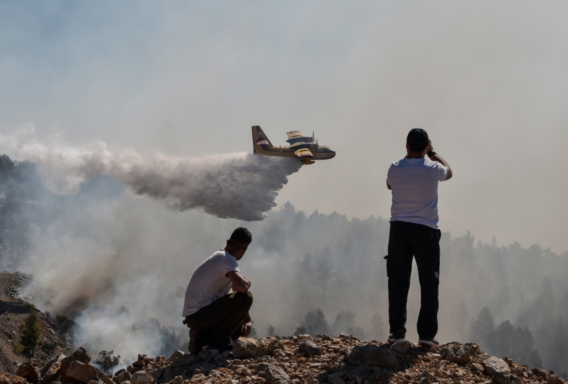 Locals watch a firefighting plane drop water over the wildfire near the village of Stavros. [Louisa Gouliamaki/AFP]