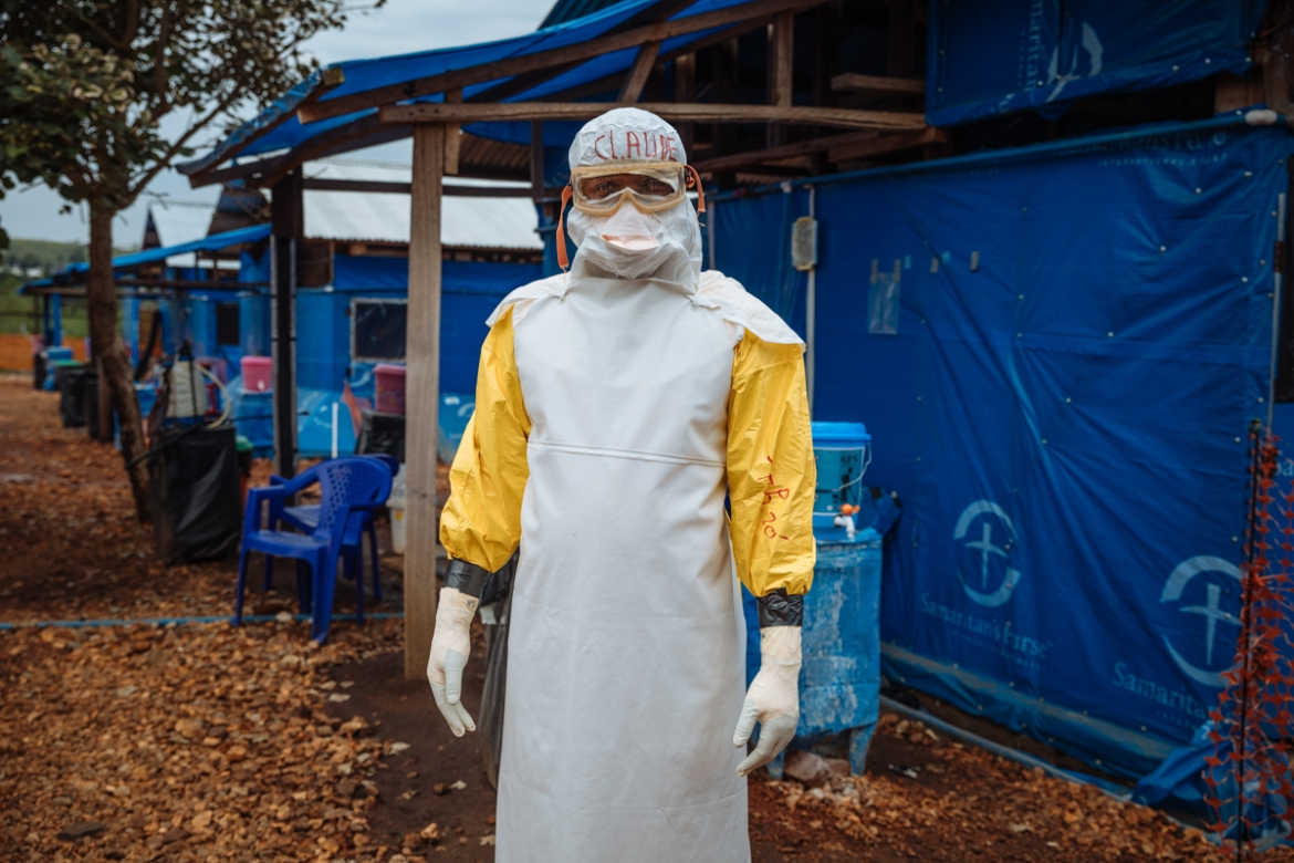 The centre has treated more than 600 suspected or confirmed cases of Ebola since the outbreak reached the area. Their staff includes health workers like Claude who come from the local community. 'It is really hot inside this suit, but we are used to it. It's our work. At the beginning we were fearful, but now I feel more secure here than at a normal hospital.' [Muse Mohammed/IOM]