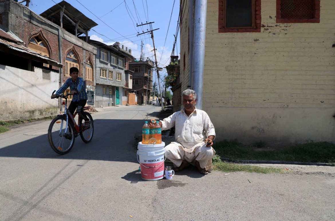 Muhammad Ayoub, an autorickshaw driver, sells petrol outside his house in Rainawari area of Srinagar. 'I used to earn a handsome amount of money by riding autorickshaw in the city but now I have no option other than this to feed my family,' Ayoub said. 'We saw many unrest in Kashmir in the past but this time it is something different. It's about the land and our identity,' he said. [Syed Shahriyar/Al Jazeera]