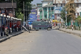An armoured Indian police vehicle blocks a road during the curfew in central Srinagar [Dar Yasin/AP Photo]