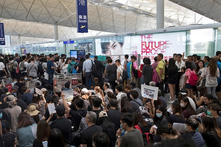 Tuesday's suspension comes a day after a pro-democracy protest brought the air transport hub to a standstill. [Vincent Thian/AP]