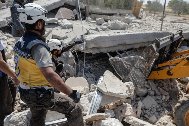 Members of the Syrian Civil Defense  search for victims at the site of a reported regime air strike on the village of Deir Sharqi [AFP]