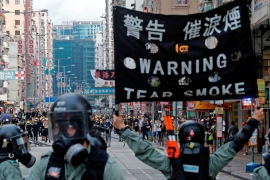 A riot police raises a warning flag as they try to disperse anti-extradition bill protesters by tear gas [Reuters]