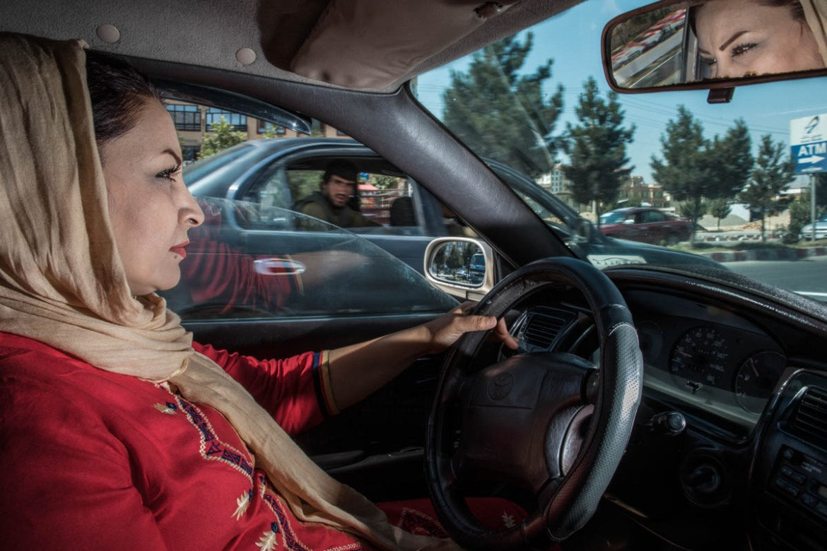 Parisah, 36, driving in Kabul. She is a former journalist who has been selected to become one of the Pink Shuttle drivers. [Alessio Mamo/Al Jazeera]