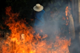 A man works in a burning tract of Amazon jungle as it is being cleared by loggers and farmers in Iranduba, Amazonas state [Bruno Kelly/Reuters]