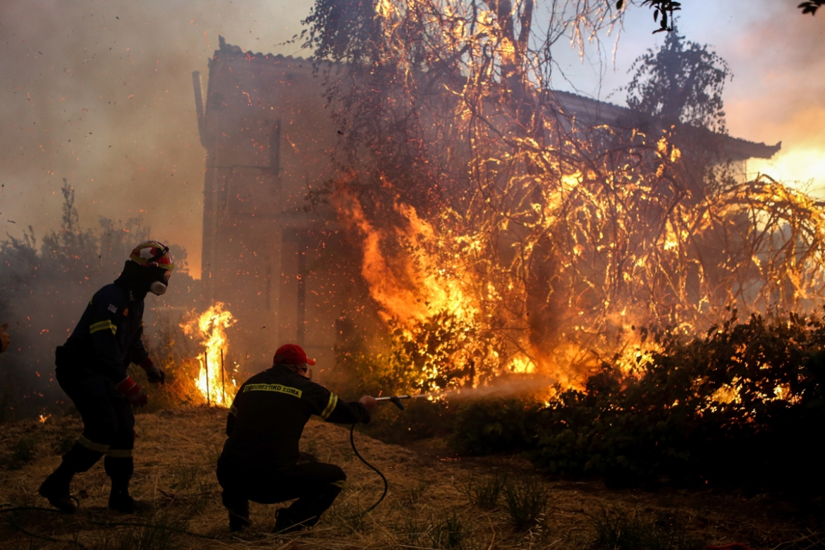 Firefighters try to extinguish the flames outside a house in Agrilitsa village. [Dimitris Kapadais/InTime News via AP]