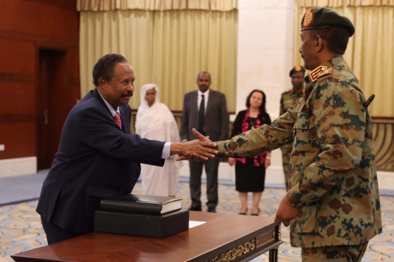 Abdalla Hamdok, left, shakes hands with General Abdel Fattah al-Burhan after being sworn in as prime minister on August 21, 2019 [File: Marwan Ali/EPA-EFE]