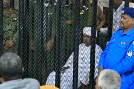 Sudan's deposed ruler Omar al-Bashir sits in a defendant's cage during the opening of his corruption trial in Khartoum [Ebrahim Hamid/AFP]