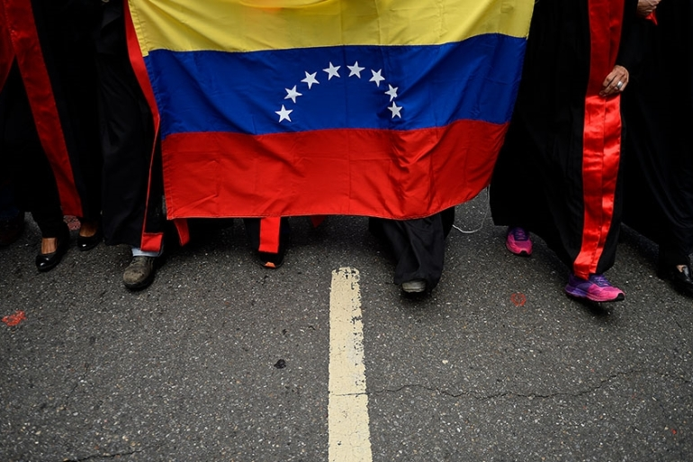 A group of lawyers dressed in judicial robes and carrying a Venezuelan national flag protest outside Venezuela's Supreme Court of Justice building against the absence of the rule of law in Venezuela at Chacao neighbourhood, in Caracas [Matias Delacroix/AFP]