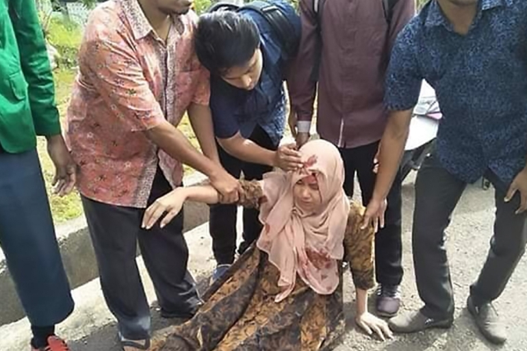 People help an injured woman in Ambon in Indonesia's Maluku islands, after the area was stuck by an earthquake on Thursday  [Aisyah Putri/AFP]