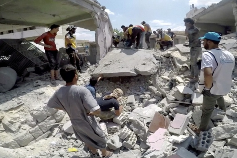 Rescuers cut through the rubble after an air raid in Idlib in July [White Helmets via Reuters]