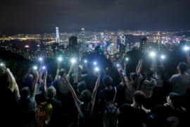 Demonstrators hold up their mobile phones as they form a human chain at the Peak, a tourist spot in Hong Kong [Kin Cheung/AP]