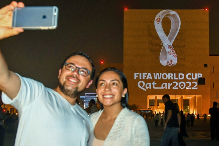 A couple take a seflie while the official emblem for the FIFA World Cup Qatar 2022 is displayed on the facade of the Musheireb Downtown Doha building at Souq Waqif in Doha, Qatar on September 3 [EPA]
