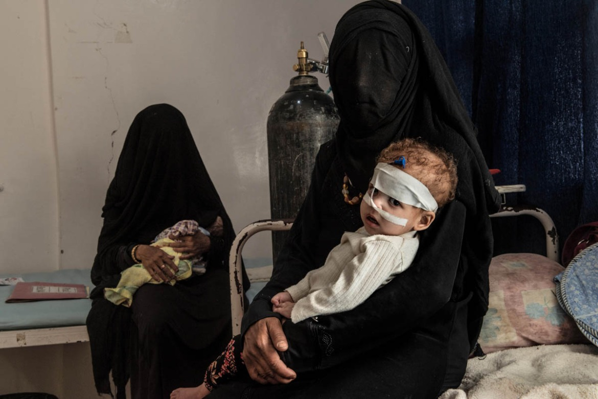 A mother with her children at Saada hospital. The city, a Houthi rebel stronghold, has been badly hit by Saudi-led coalition air attacks. [Alessio Romenzi/Al Jazeera]