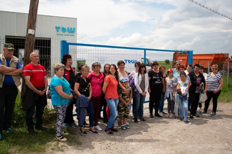 Workers protest against unpaid salaries in front of Textile Blue Wash factory in Covasna, a town in Romania's central Transylvania region, after the plant unexpectedly closed [Elisa Oddone/Al Jazeera]