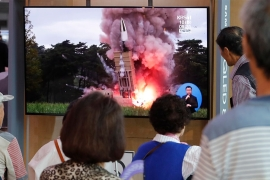 People in South Korea watch TV news reports showing file pictures on North Korea's latest missile launch.  [Ahn Young-joon/AP Photo]