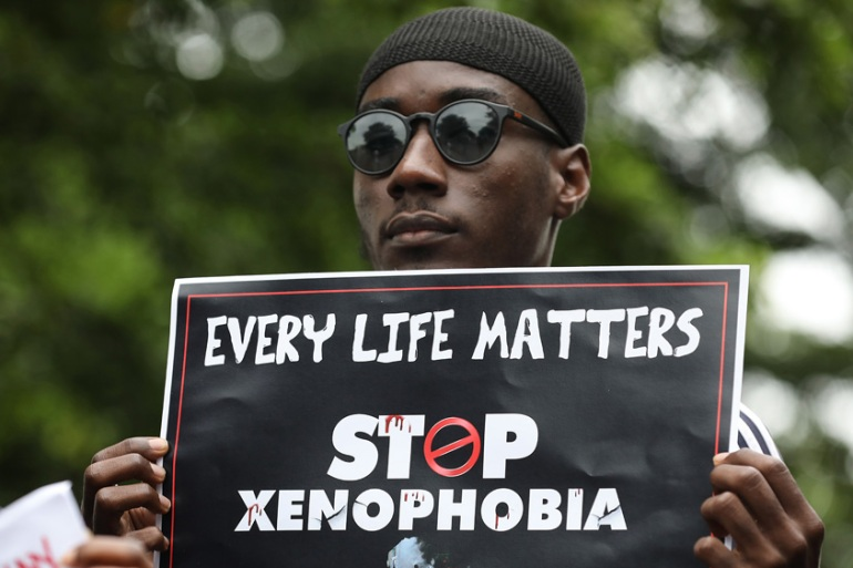 A demonstrator holds a sign during a protest against xenophobia in Abuja, Nigeria [Kola Sulaimon/AFP]
