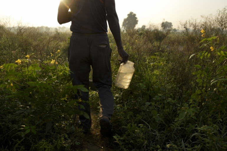 A man carrying water while going to defecate in the open in Greater Noida on the outskirts of New Delhi [File: RS Iyer/AP]