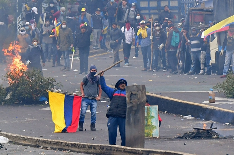 Demonstrators confront riot police during clashes around the national assembly in Quito [Martin Bernetti/AFP]