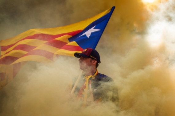 A man holding an independence flag is seen through the smoke thrown by demonstrators during the Catalan National Day in Barcelona, Spain, Wednesday, Sept. 11, 2019 [AP Photo/Emilio Morenatti]