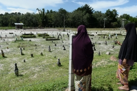 In this photo taken on October 24, 2019, widow Sitirokayah Salaeh (R) visits the cemetery in Tak Bai where her late husband Mahamad Lohbako is buried together with other anti-government demonstrators who died during the 2004 Tak Bai incident, in Thailand''s southern province of Narathiwat [Madaree Tohlala/AFP]