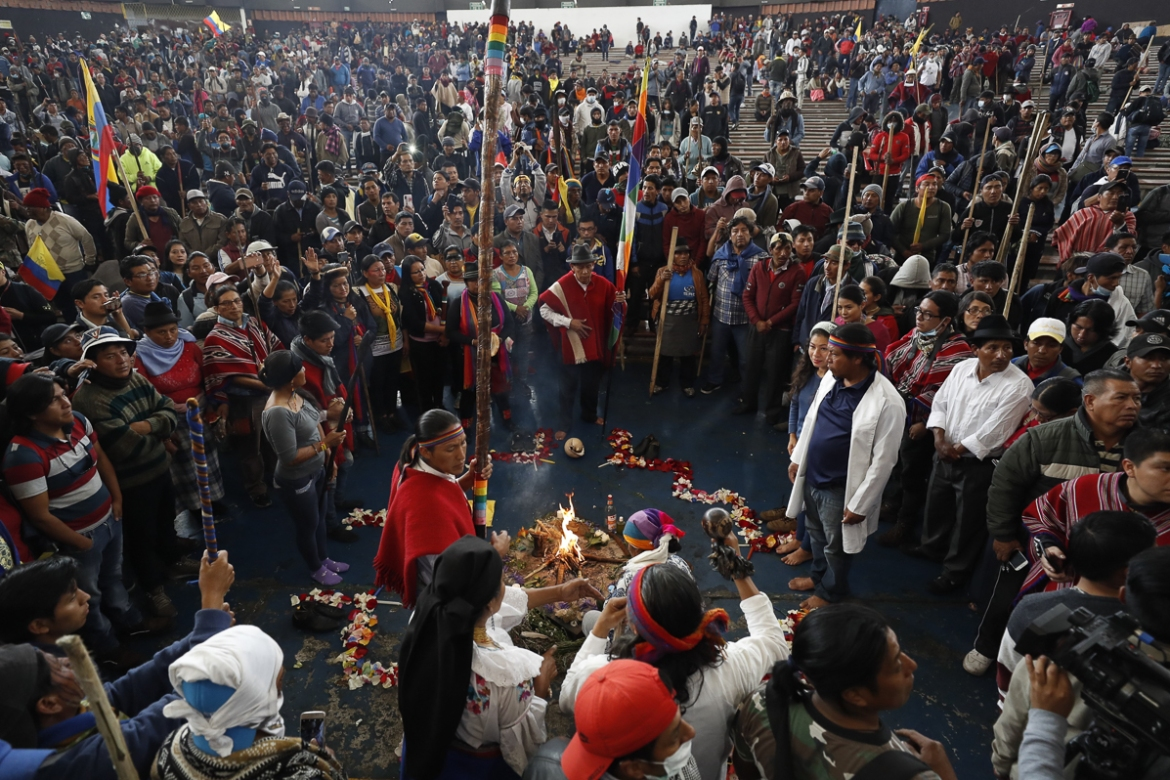 Indigenous people perform a ritual during the protest in Quito. [Paolo Aguilar/EPA]