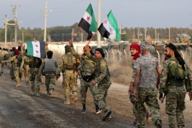 Turkey-backed Syrian rebel fighters hold the Syrian opposition flag as they walk together in the border town of Akcakale in Sanliurfa province, Turkey, October 11, 2019 [Khalil Ashawi/Reuters]