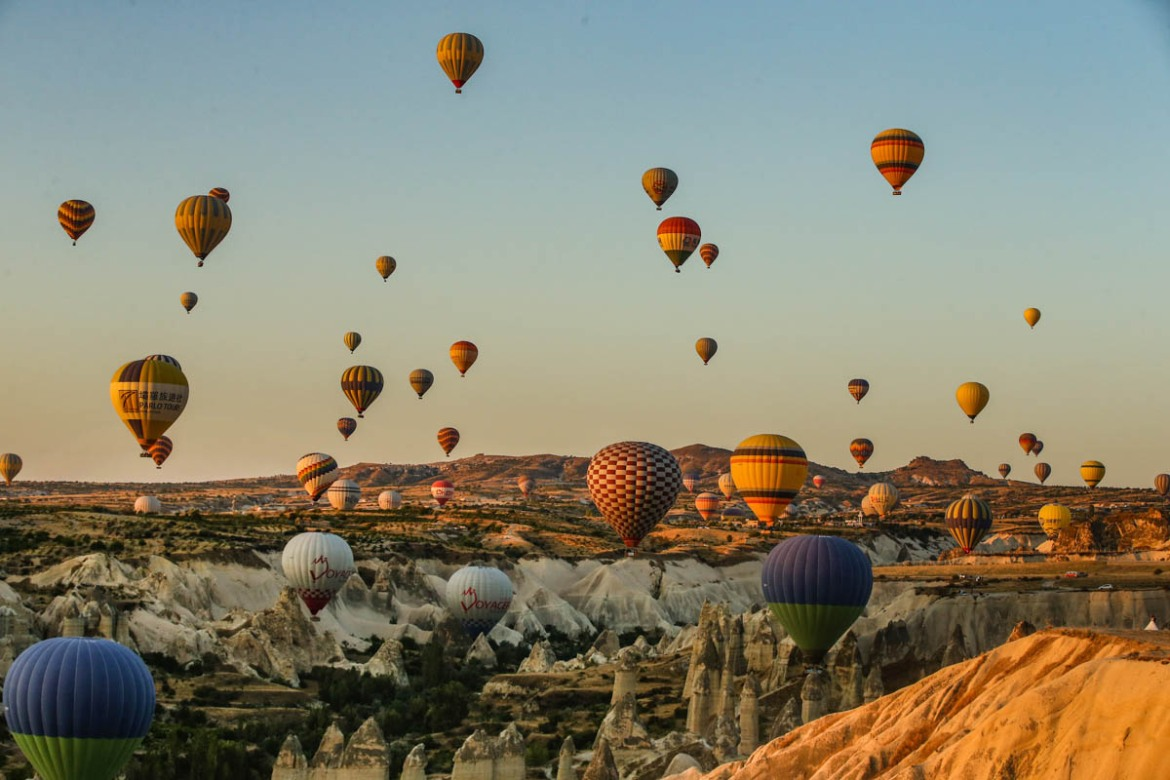 Hot air balloons filled with tourists rise into the sky at sunrise in Cappadocia, central Turkey. [Emrah Gurel/AP Photo]