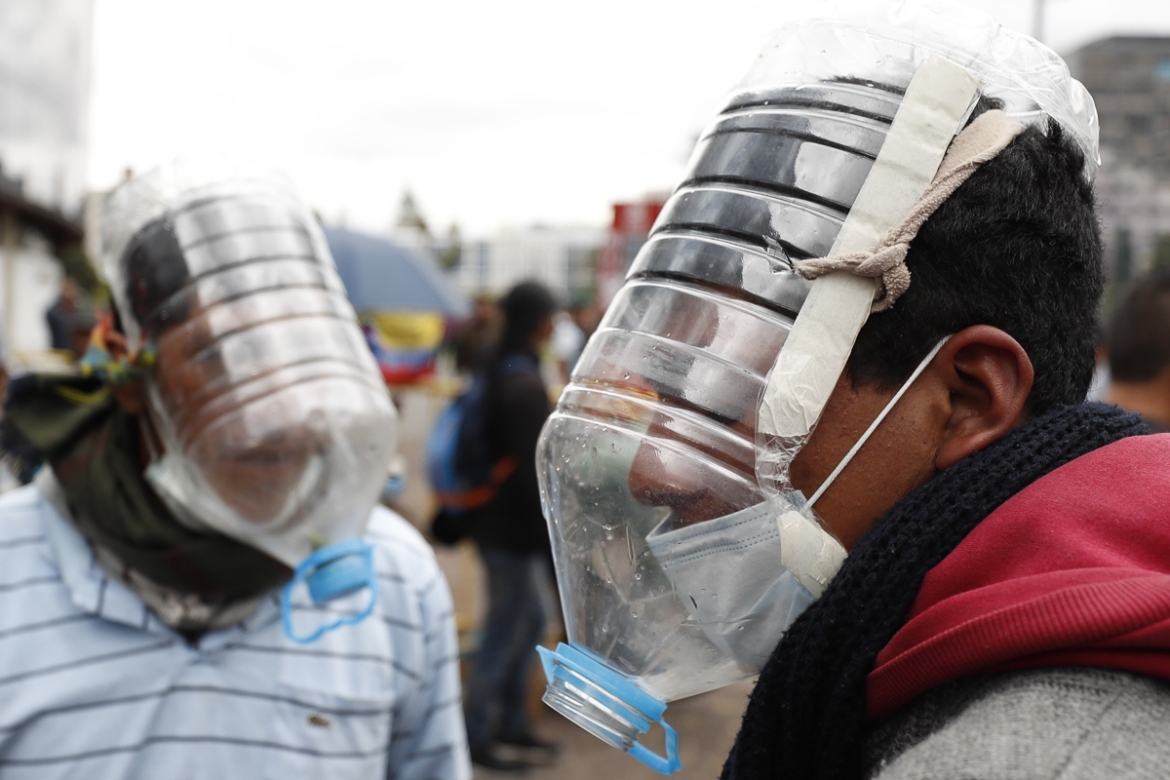 People use homemade masks to face tear gas attacks during clashes. Thousands of individuals from disadvantaged indigenous communities in the Amazon and the Andes travelled to Quito where they are spearheading demands that the subsidies return. [Paolo Aguilar/EPA]