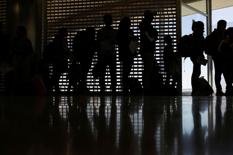 Honduran migrants stand in line at the airport after giving up their US asylum claims and voluntarily returning to Honduras, in Ciudad Juarez, Mexico [Jose Luis Gonzalez/Reuters]