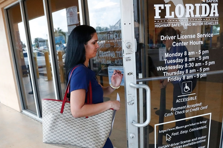 A woman enters a Florida Highway Safety and Motor Vehicles drivers license service centre in Hialeah, Florida [Wilfredo Lee/AP Photo]