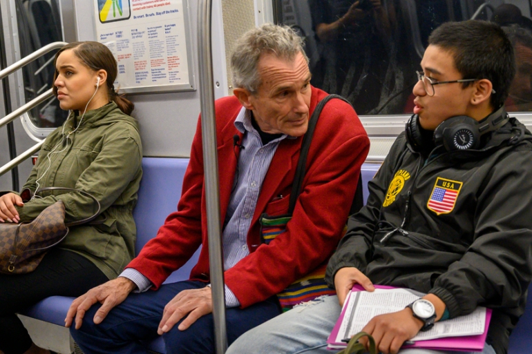 Richard McLachlan speaks with subway rider Anthony Urias about climate change [Don Emmert/AFP]