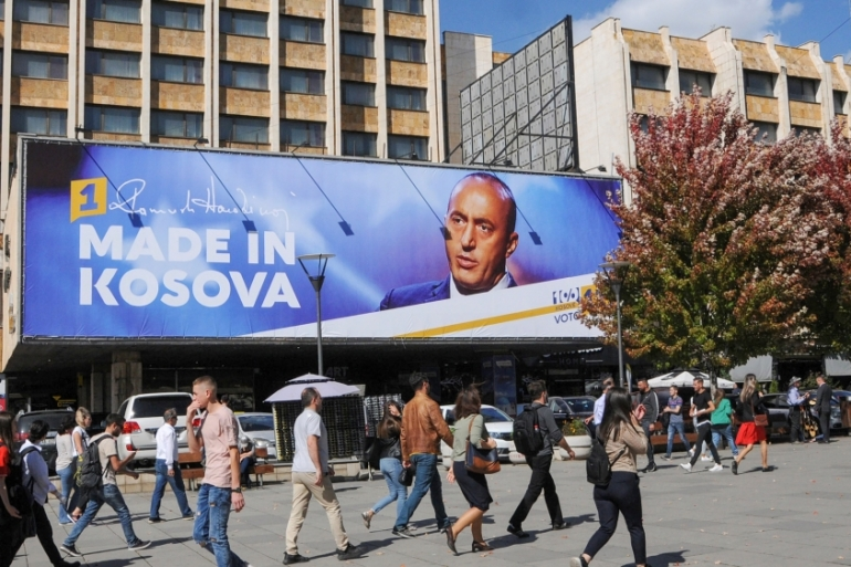 People walk past a billboard showing Ramush Haradinaj, leader of the Alliance for the Future of Kosovo (AAK), in Pristina [Laura Hasani/Reuters]