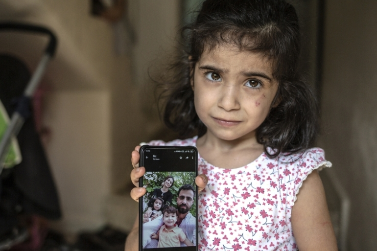 The four-year-old daughter of Hassan Muhamed shows a picture of him [Hosam Salem/Al Jazeera]
